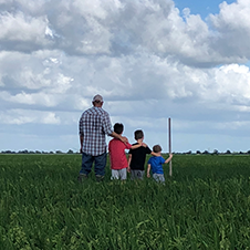 Farmer standing in a rice field with three sons