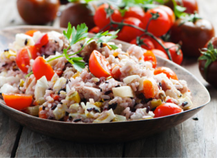 Side view of a healthy rice salad in a serving bowl.