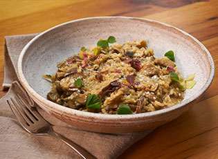 Side view of Fall Mushroom Risotto in a white bowl.