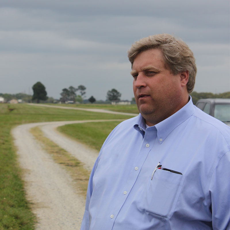 Rice farmer, Nat McKnight, standing on a country road.