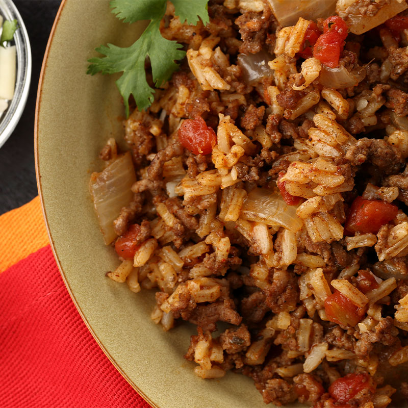 Zoomed in view of a plate full of a white rice and ground beef mixture with onions and tomatoes.