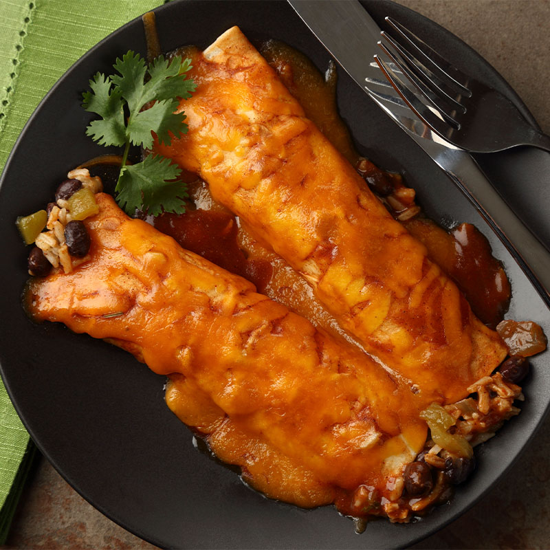 Overhead image of two enchiladas covered in sauce on a black plate.