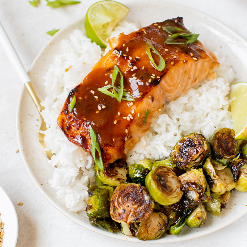A cut of Brown Sugar Glazed Salmon on a bed of white rice.
