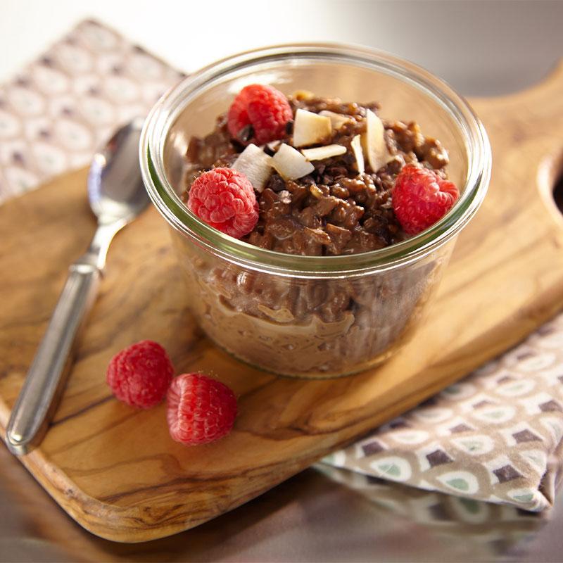 Chocolate Espresso Porridge topped with Raspberries in a glass jar.