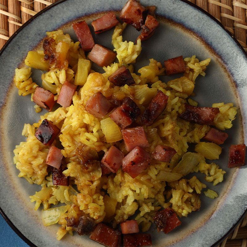Overhead view of cubed ham and pineapple pieces sit on top of a bed of yellow rice.