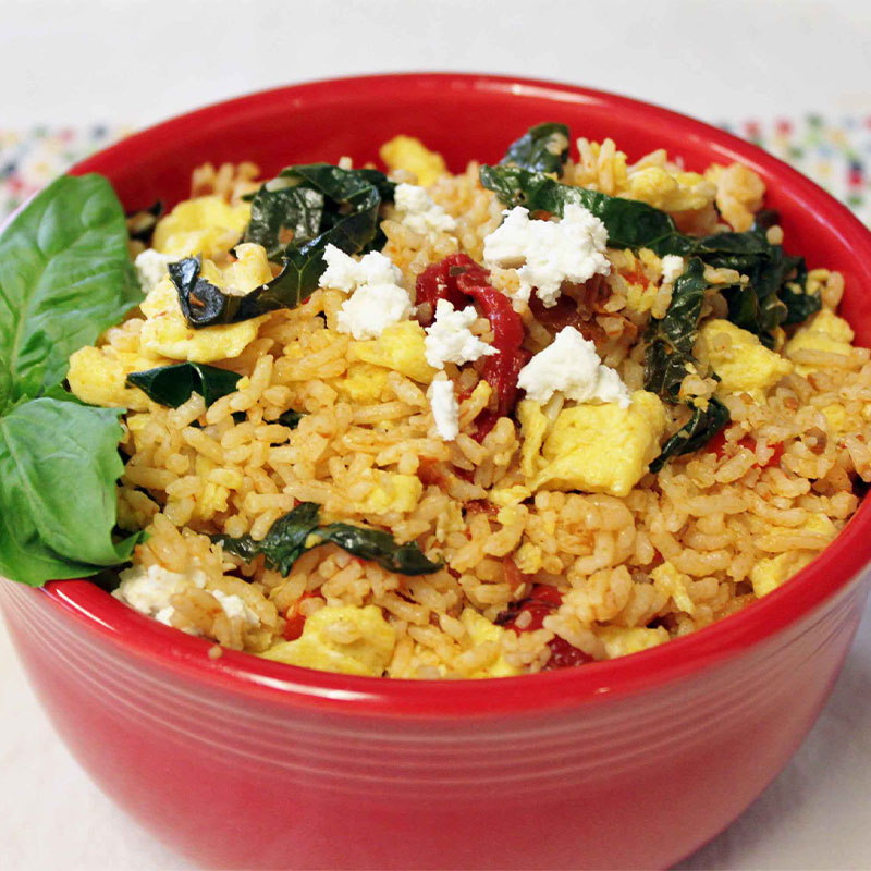 A serving of Mediterranean Breakfast Kale Rice in a red bowl and garnished with basil.