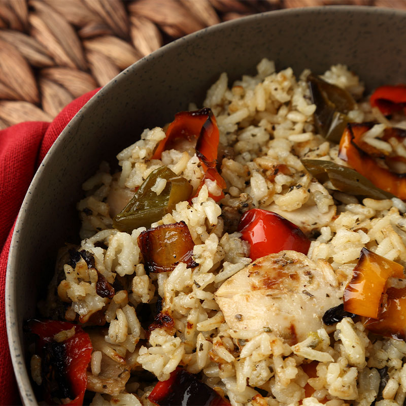 A zoomed in shot of white rice, chicken, and roasted peppers in a bowl.