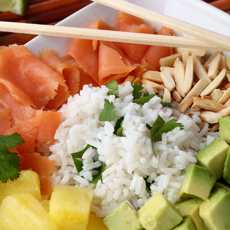 Overhead shot of a neatly arranged Smoked Salmon and Avocado Breakfast Rice Bowl with ginger and pineapple chunks.