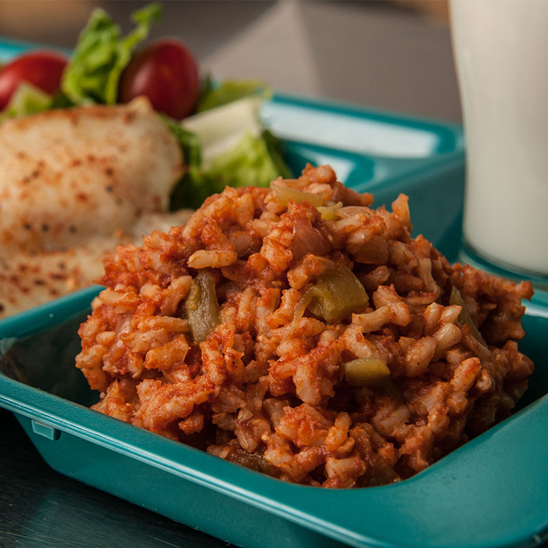 Side view of Spanish Brown Rice on a school lunch tray.