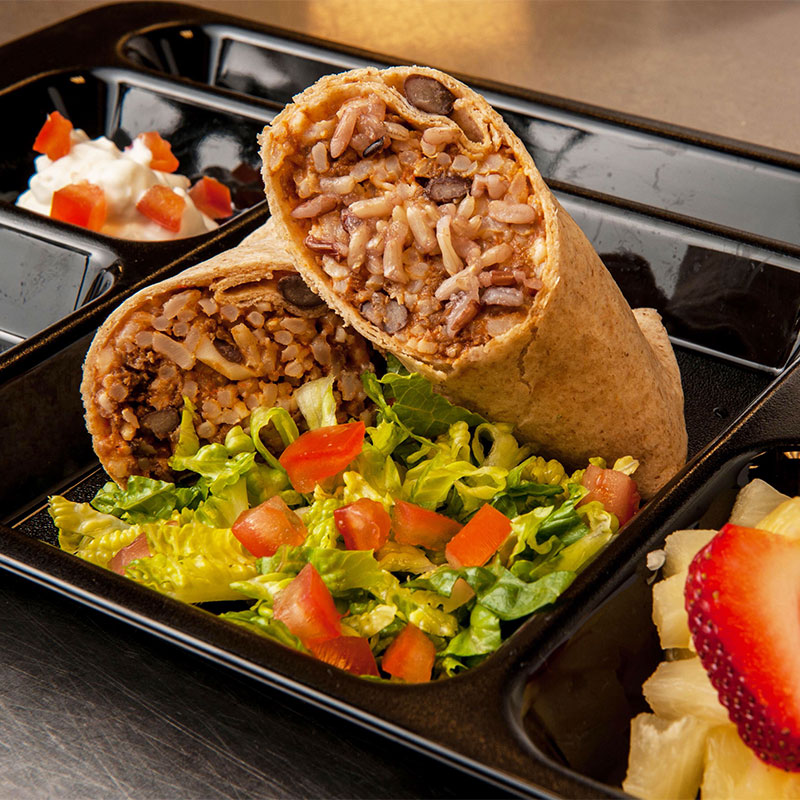Two stuffed beef burritos stacked on top of each other and on a black cafeteria tray.
