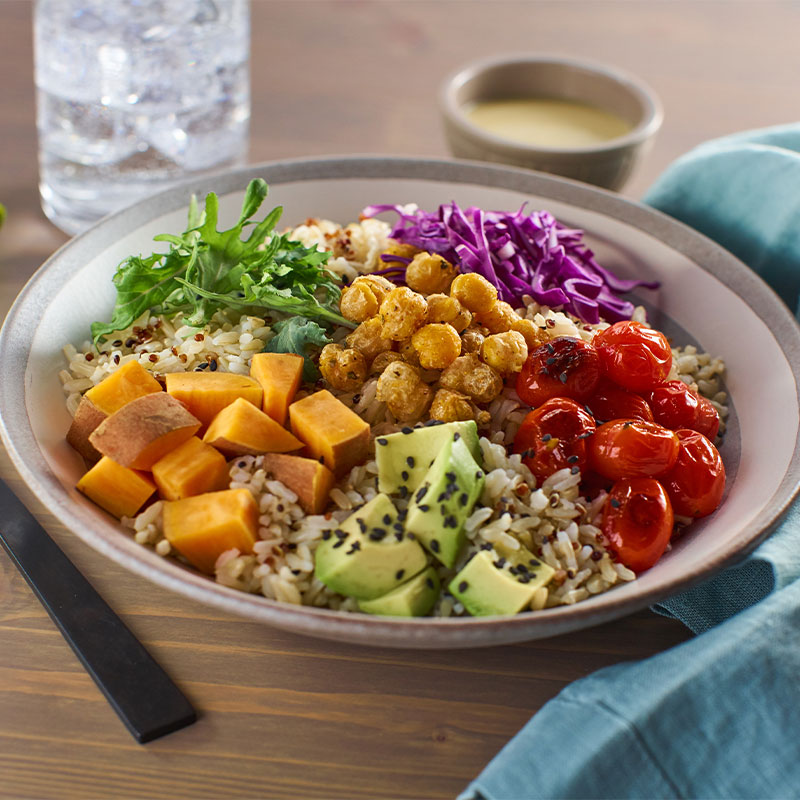 A brown rice bowl topped with chickpeas, avocado pieces, red cabbage, sweet potato chunks, and baby red tomatoes.
