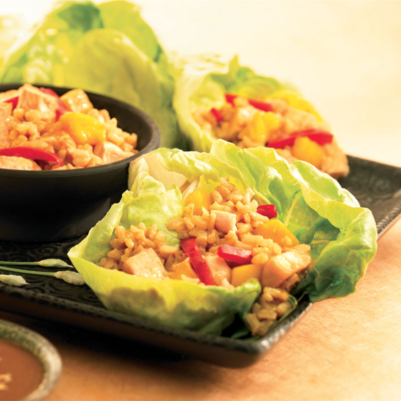 Two lettuce leaves filled with Thai Chicken and Brown Rice next to a black bowl filled with the chicken and rice.