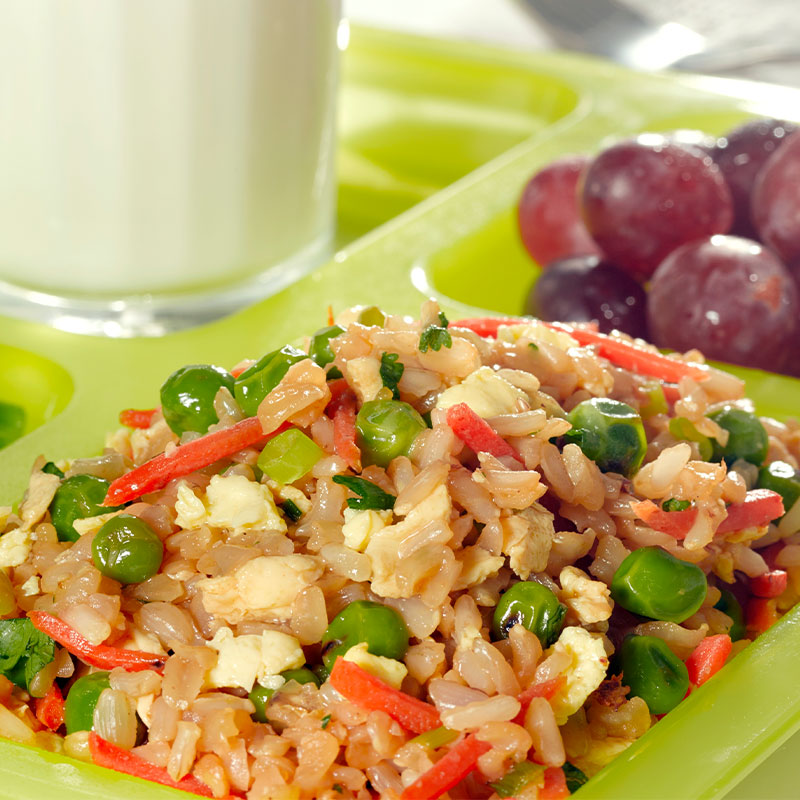 A serving of Vegetable Fried Brown Rice in a green cafeteria tray with grapes and broccoli.