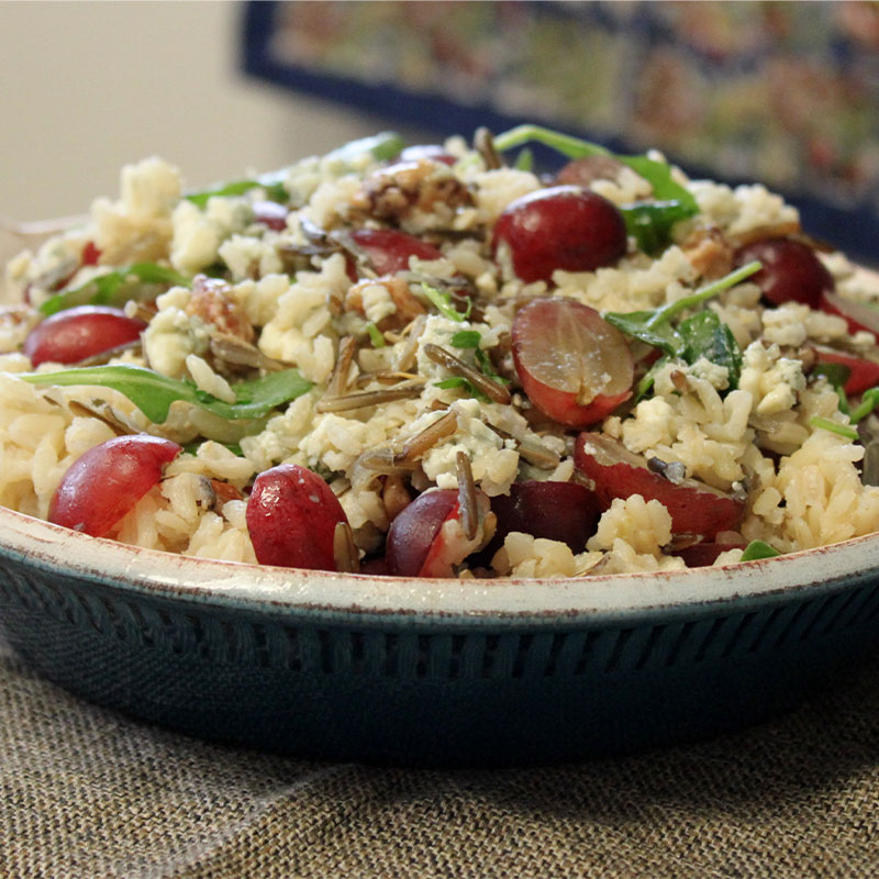 Side view of a wild and brown rice bowl topped with roasted red grapes.