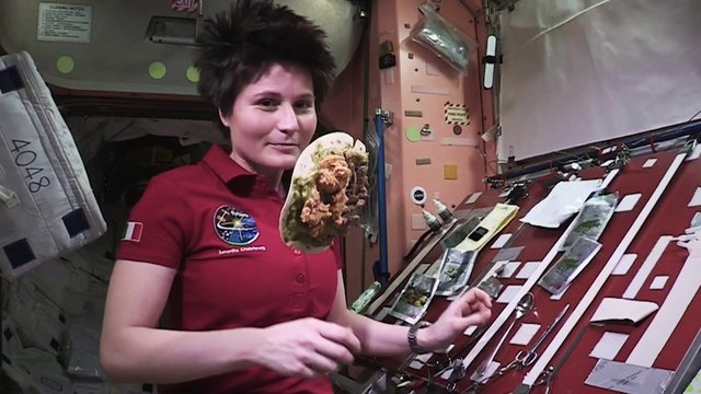 Female astronaut Samantha Cristoforetti wearing maroon shirt, cooks in zero gravity with food floating in space