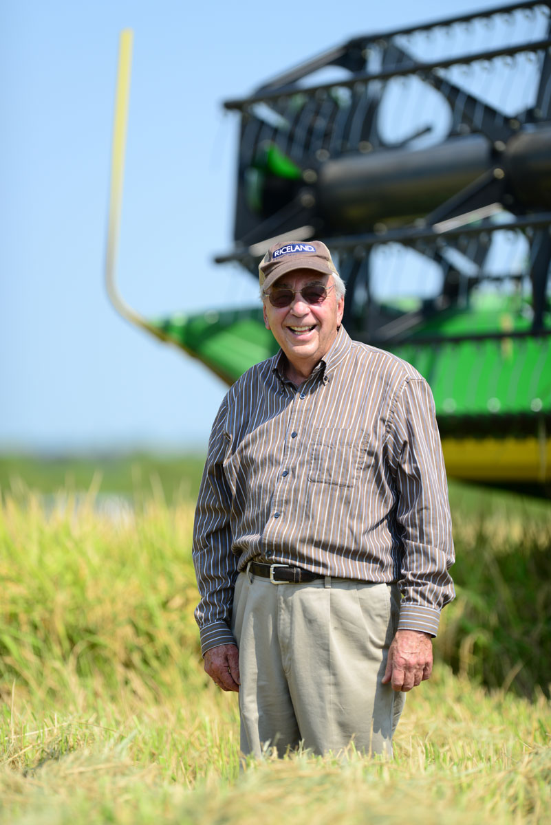 Older white man wearing ballcap, standing in front of green combine