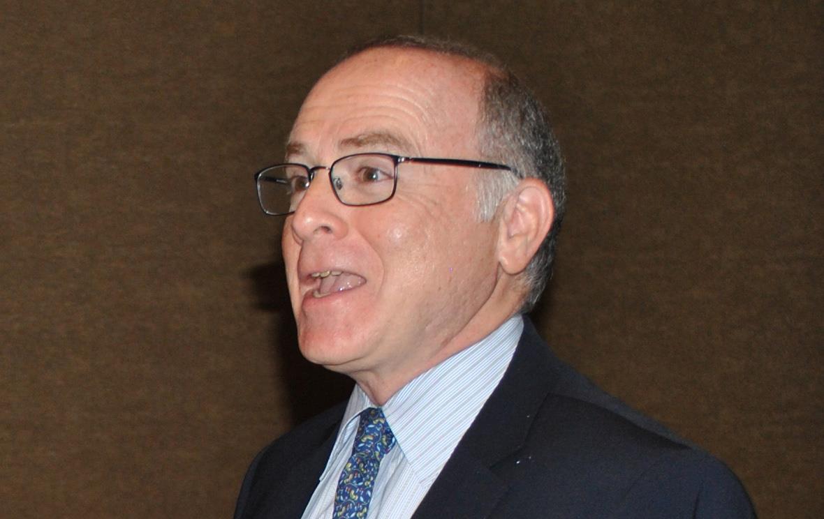 Man wearing glasses & dark business suit, laughing