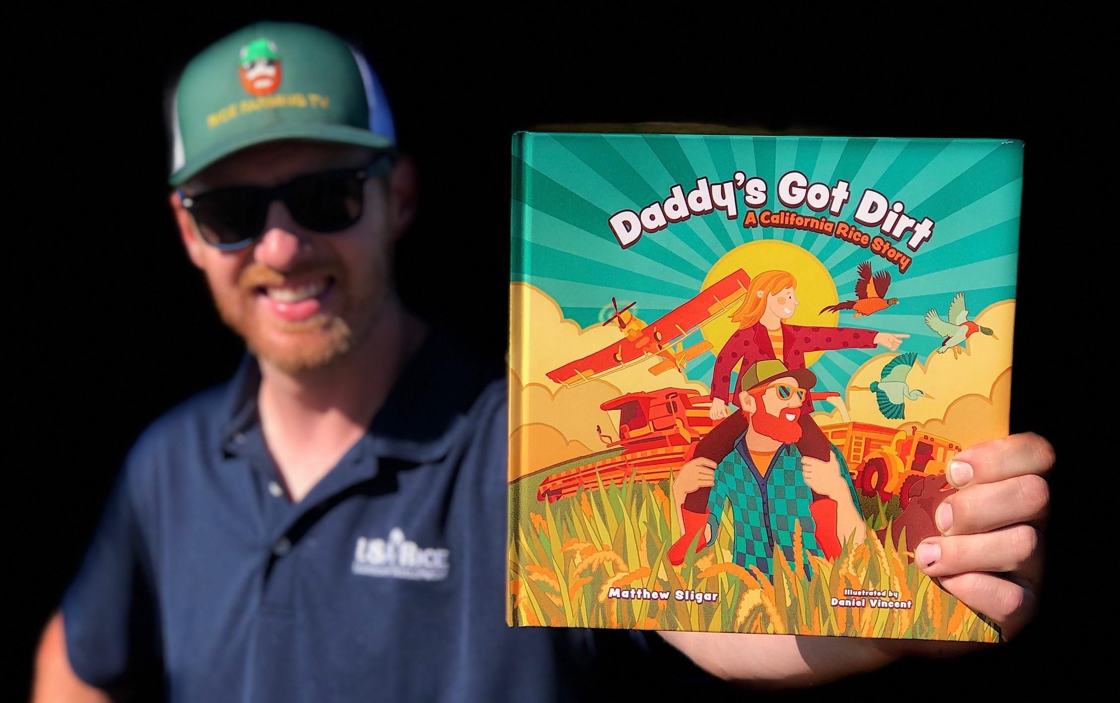 White man wearing ballcap holds childrens book, Daddy
