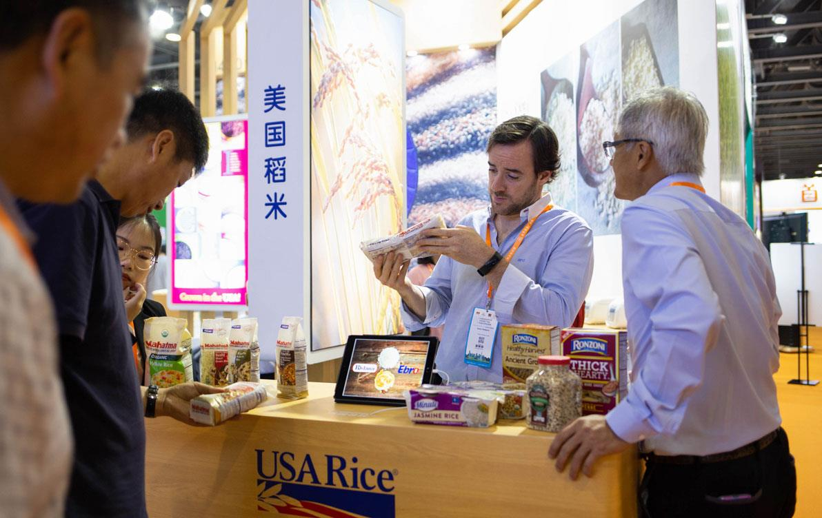 Trade-show-booth, group of men examine rice products displayed on table