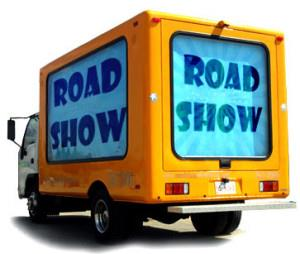 "Moving truck with white cab and yellow body with text ""Road Show"" on blue background"