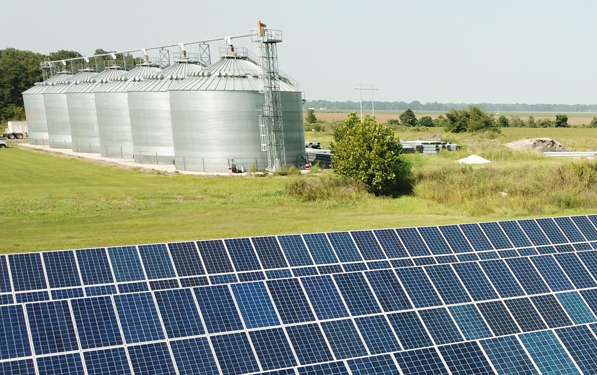 Rows of blue solar panels in a green field with grain bins in the background