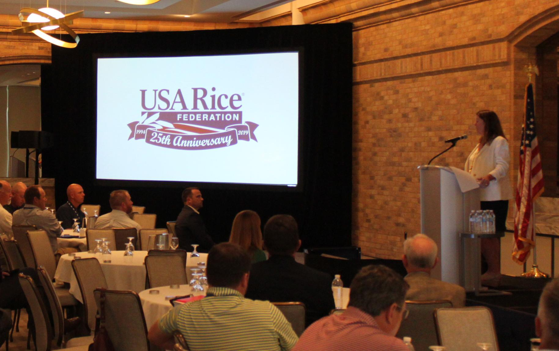 """Crowded meeting room, woman standing at podium next to projected slides that reads: """"USA Rice Federation 25th Anniversary"""""""