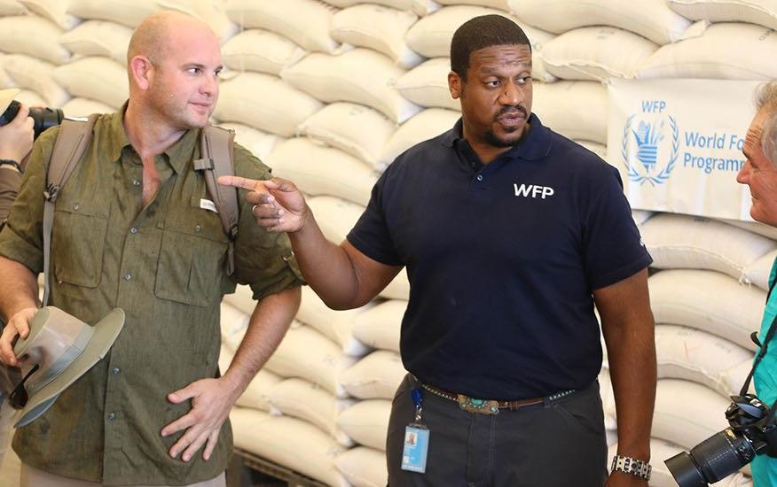 Men stand in front of pallets of bags of rice