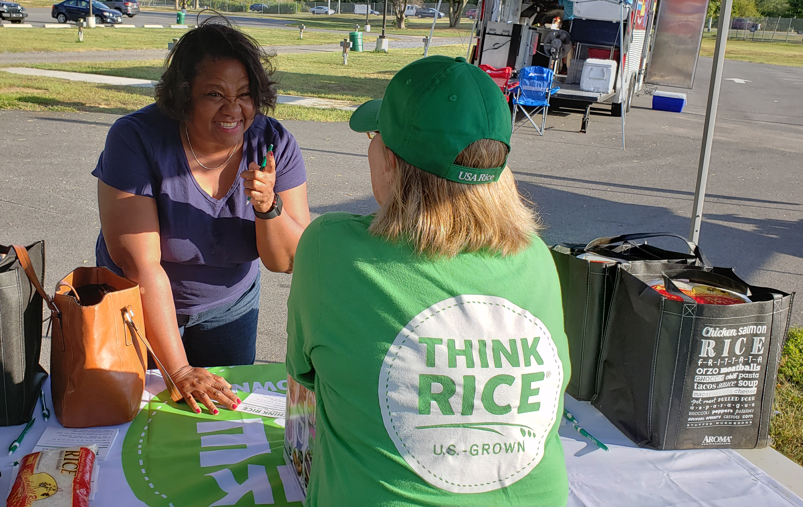 Woman stands across a table and shakes her finger at woman with back to camera wearing a green Think Rice shirt