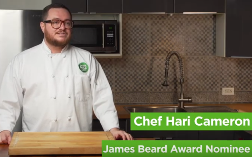 Chef Hari Cameron wearing white chef jacket with green Think Rice logo stands in kitchen, cutting board on table in front of him