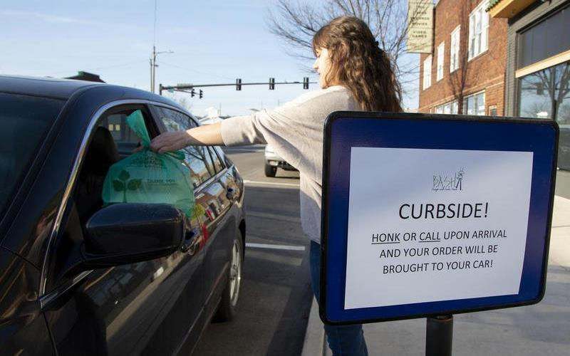 """Woman on sidewalk hands bag of food to person in car, signage reads: """"Curbside! Honk or call upon arrival & order will be brought to your car!"""""""