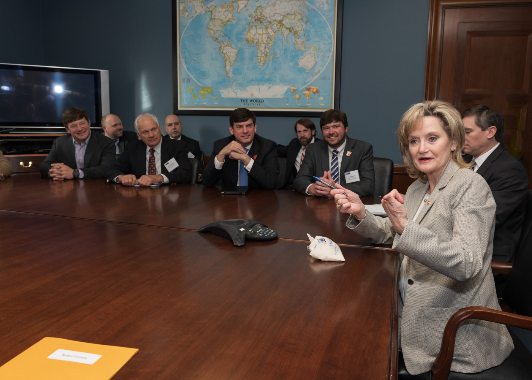 White woman holding pen and gesturing with hands holds court at table of white men wearing suits