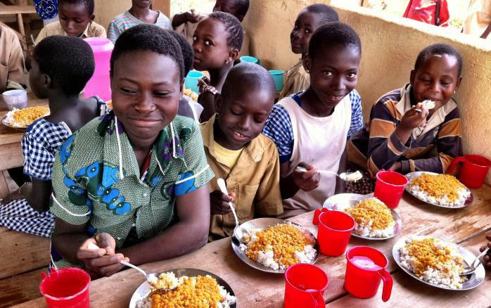 Black children eat lunch of beans and rice at wooden tables