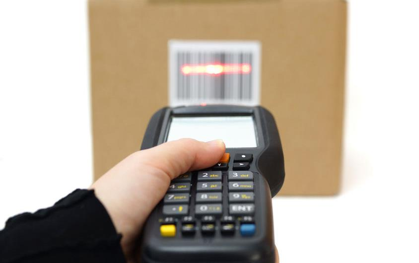 Hand holds scanner over QR codes on cardboard box