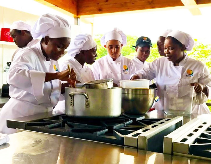 Student chefs wearing white chef jackets and toques gather around pots on stove