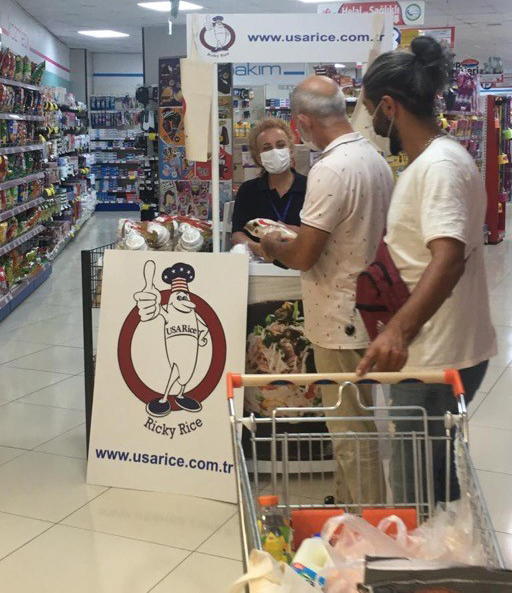 Promotion booth with Ricky Rice poster set up in grocery store is visited by customers wearing masks with shopping cart
