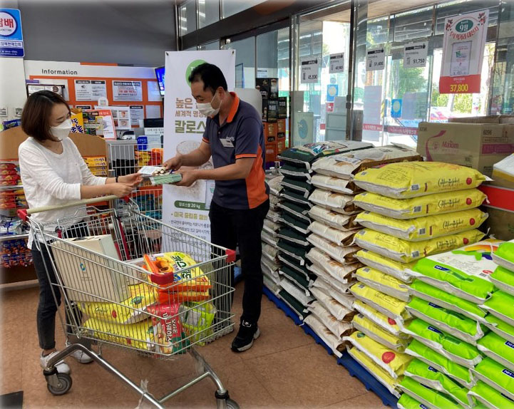 Female shopper with grocery cart talks man handing out flyers, large bags of rice stacked in background