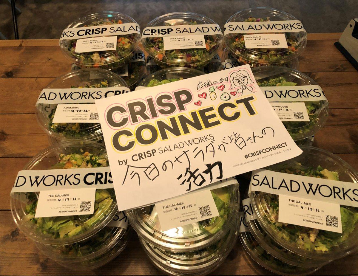 Salads in clear plastic to-go containers stacked on table under sign that reads:  Crisp Connect