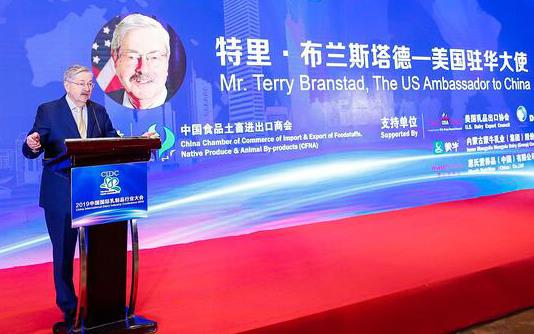 Older white man wearing business suit stands at podium with large poster welcoming Terry Branstad, US Ambassador to China
