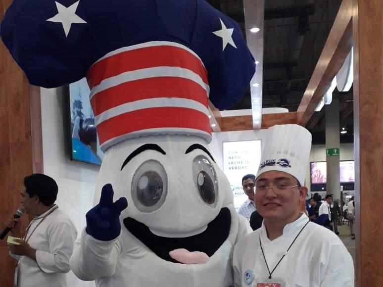 Rice mascot with big eyes and wide open mouth, wearing red, white & blue chef