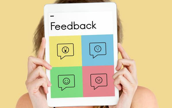 White woman holds iPad in front of her face with 4 color blocks showing different emojis