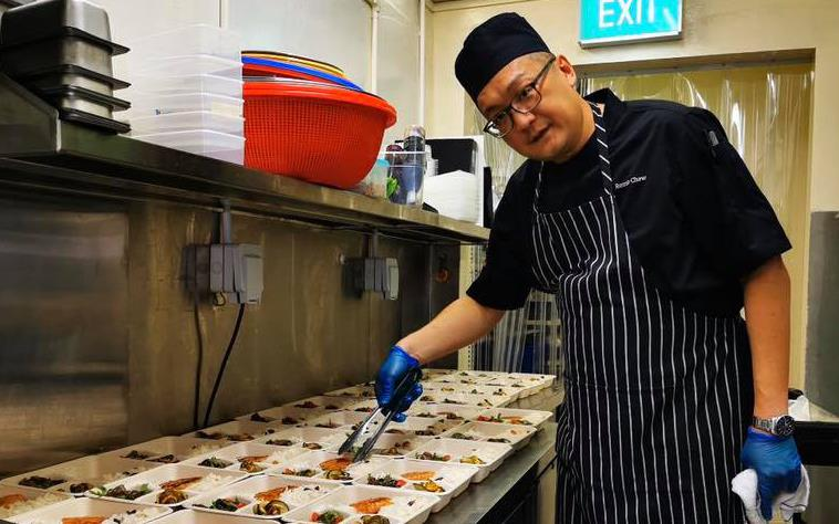 Chef wearing black apron with white stripes uses tongs to prep takeout meals in plastic containers