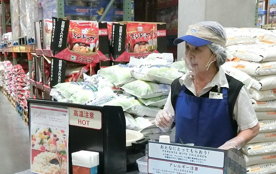 Woman wearing blue apron, hairnet, and visor stands behind metal cart handing out rice samples in paper cups