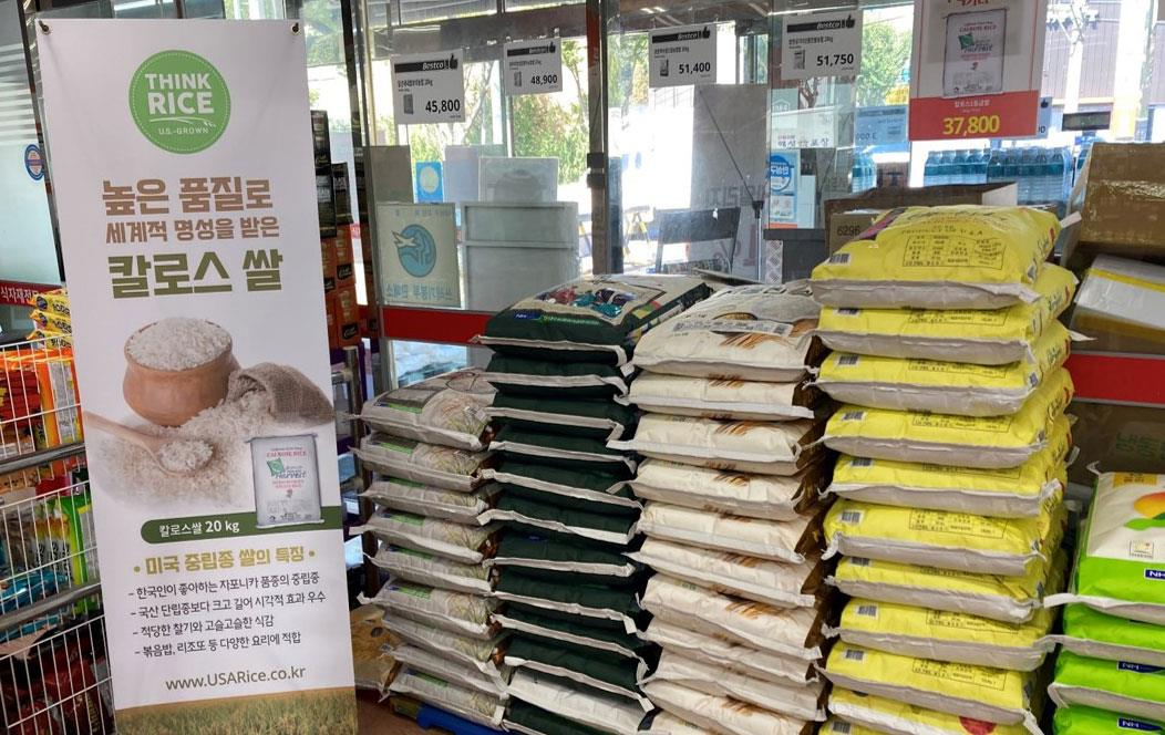 Think Rice promotion sign next to stacks of rice-bags