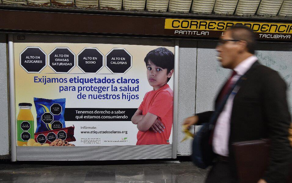 Poster in subway station shows young boy with junk food and warning labels in Spanish