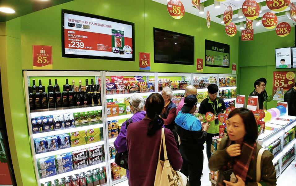 People stand in line at a small package store, lime green walls with circular banners hanging from the ceiling