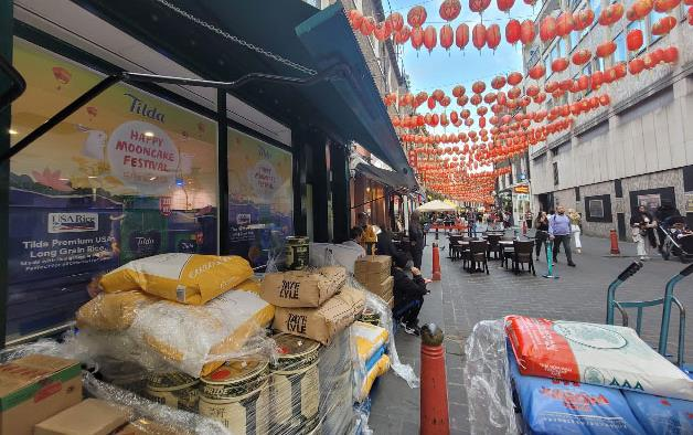 Orange lanterns strung above outdoor display with Mooncake Festival poster and bags of rice