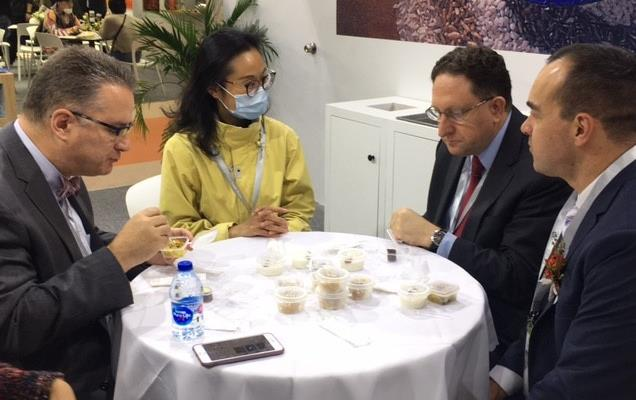 Three men and one woman sit around table filled with rice samples