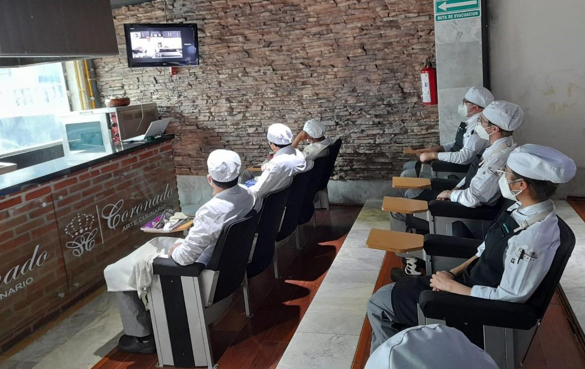 Student chefs seated at desks watch video monitor at chef workshop in Mexico