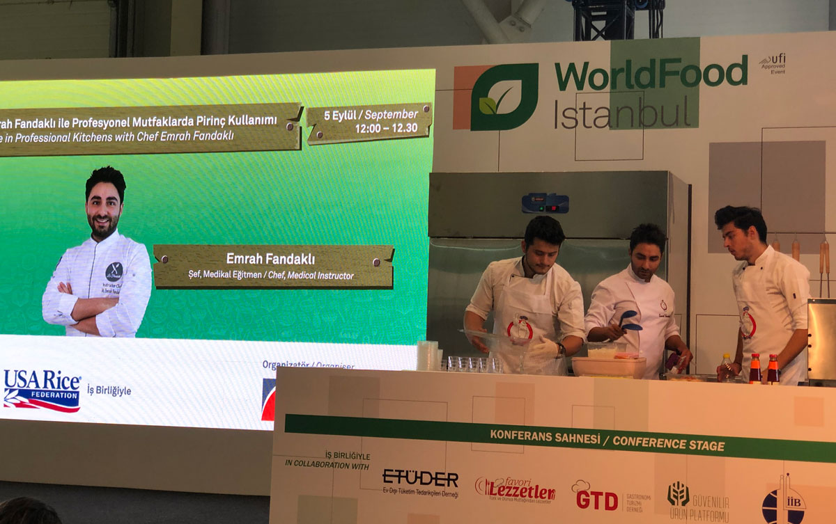 Three chefs cook on stage beside large photo of another chef with the USA Rice logo
