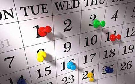 Monthly calendar with colorful thumbtacks stuck in different dates